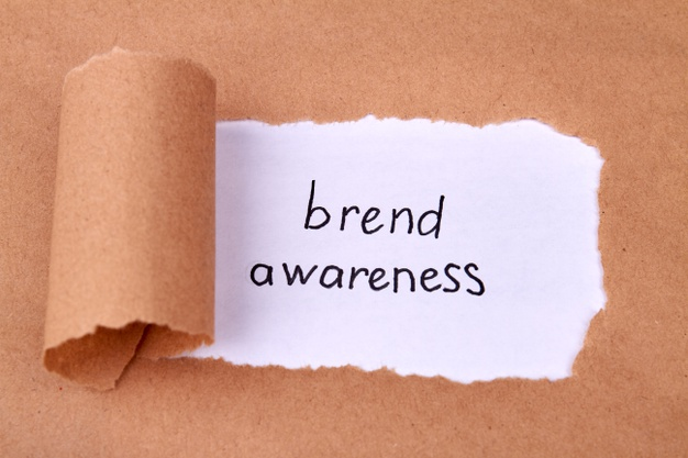 Brand awareness concept with uncovered beige paper and revealed message Premium Photo